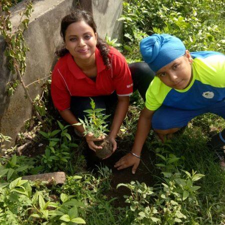 हल्द्वानी के पाथ फाइंडर बोर्डिंग स्कूल में आयोजित पौधारोपण कार्यक्रम में पेड़ लगाते बच्चे।