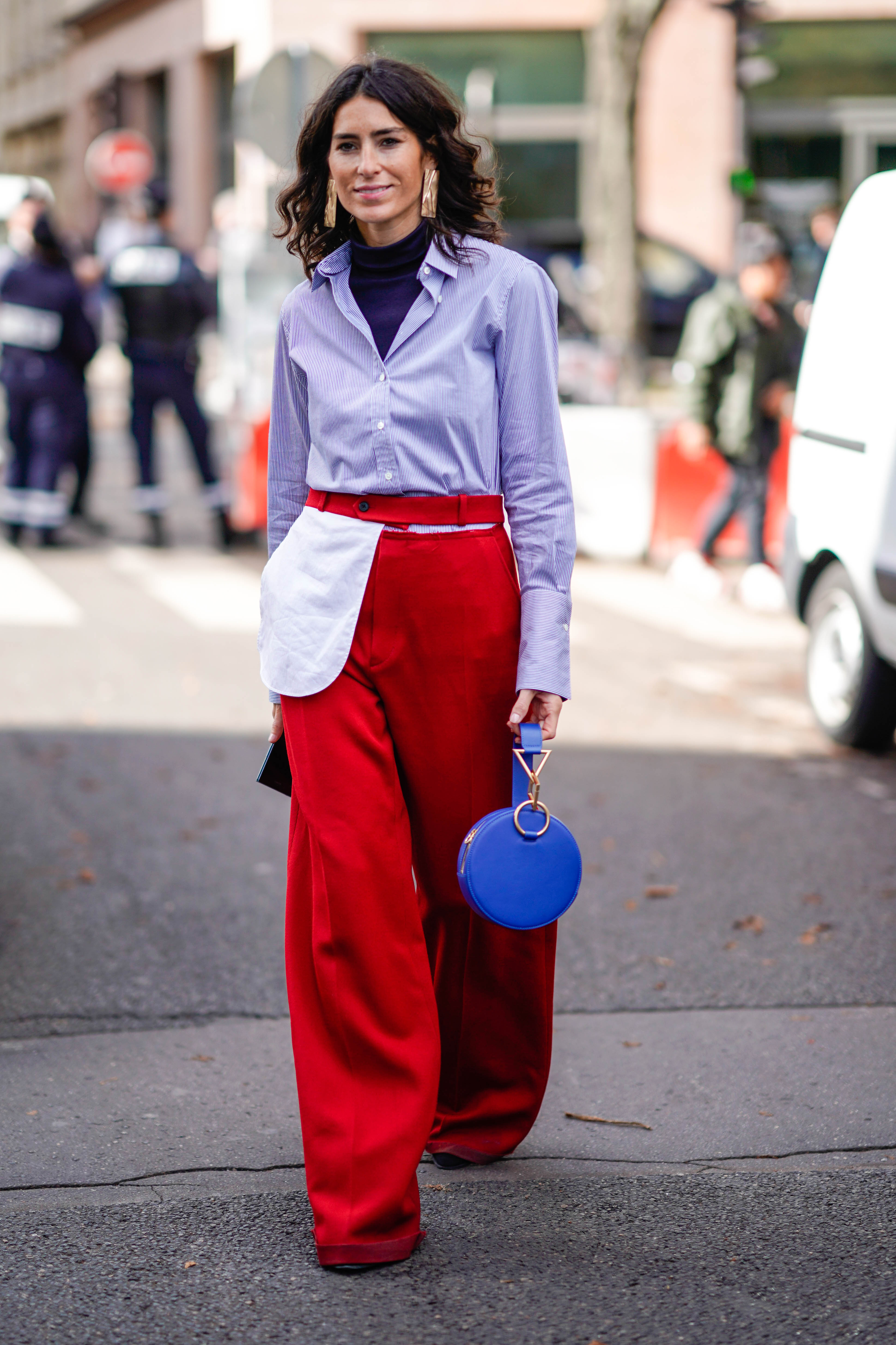 PARIS, FRANCE - OCTOBER 03: A guest wears a striped shirt, red pants, a blue bag, outside Moncler, during Paris Fashion Week Womenswear Spring/Summer 2018, on October 3, 2017 in Paris, France. (Photo by Edward Berthelot/Getty Images)